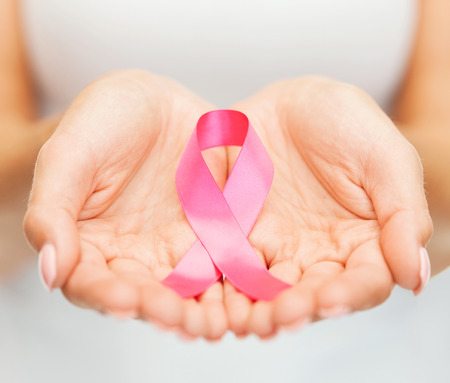 young girls breast: healthcare and medicine concept - womans hands holding pink breast cancer awareness ribbon