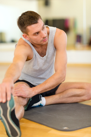 man working out: fitness, sport, training, gym and lifestyle concept - serious man stretching on mat in the gym