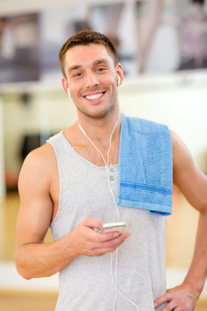 fitness, sport, training, gym, technology and lifestyle concept - young man with smartphone and towel in gym photo