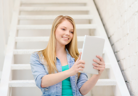 education and technology concept - smiling female student with tablet pc computer sitting on staircase photo