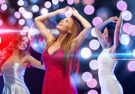 new year, celebration, friends, bachelorette party, birthday concept - three beautiful woman in evening dresses dancing in the club Stock Photo
