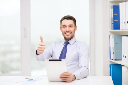 business, technology, finances and internet concept - smiling businessman with tablet pc computer and documents at office showing thumbs up photo