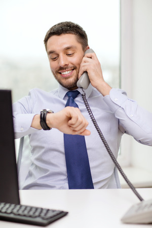 business, office and technology concept - smiling businessman making call and looking at wristwatch at office photo