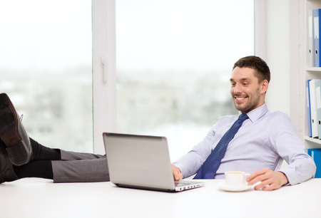 office, business, education, technology and internet concept - smiling businessman or student with laptop computer and coffee at office photo