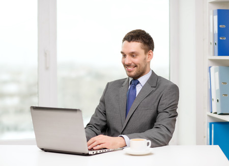 office, business, technology and internet concept - smiling businessman with laptop computer and coffee at office photo