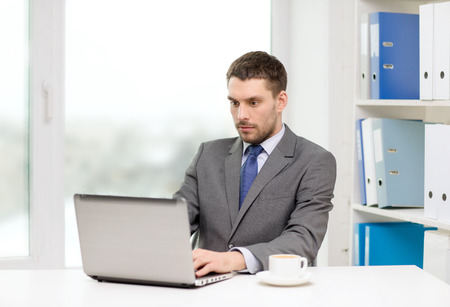serious businessman: office, business, technology and internet concept - busy businessman with laptop computer and coffee at office