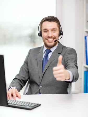 business, communication and technology concept - friendly male helpline operator with headphones and computer at call center showing thumbs up photo