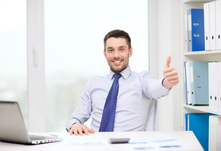 business, technology, finances and internet concept - smiling businessman with laptop computer and documents at office showing thumbs up