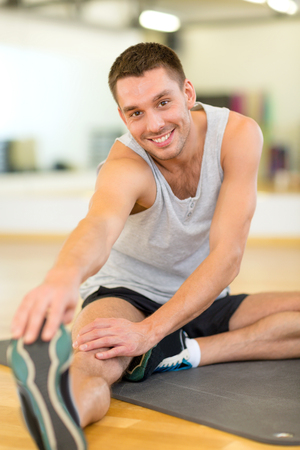 fitness, sport, training, gym and lifestyle concept - smiling man stretching on mat in the gym photo