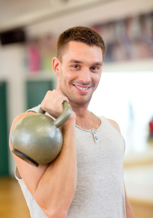 fitness, sport, training, gym and lifestyle concept - smiling man with kettlebell in gym photo