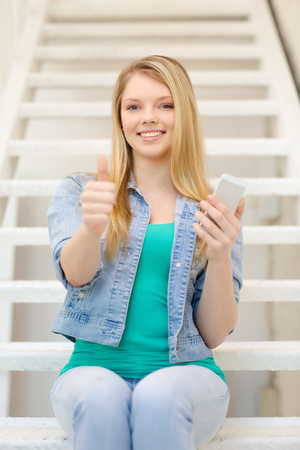 education and technology concept - smiling female student with smartphone sitting on staircase and showing thumbs up photo