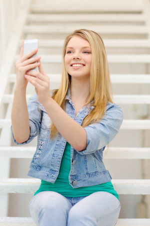 education and technology concept - smiling female student with smartphone sitting on staircase and taking picture photo