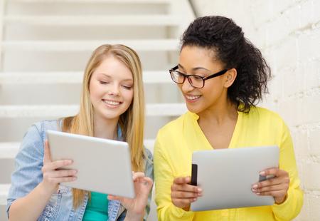education and technology concept - smiling female students with tablet pc computer sitting on staircase photo