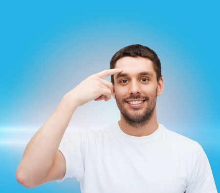 health and beauty concept - smiling young handsome man pointing to forehead photo