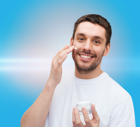 aftershave: health and beauty concept - beautiful smiling man with jar of cream applying cream Stock Photo