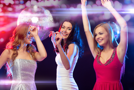 night out: new year, celebration, friends, bachelorette party, birthday concept - three beautiful woman in evening dresses dancing in the club Stock Photo