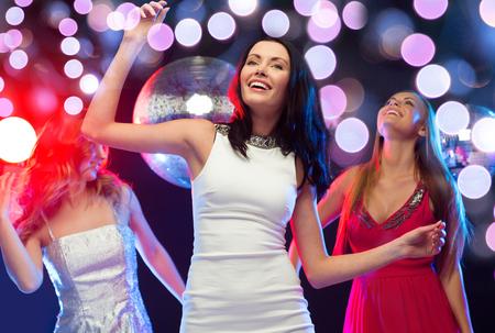 despedida de soltera: año nuevo, celebración, amigos, despedida de soltera, cumpleaños concepto - tres hermosa mujer en vestidos de noche bailando en el club