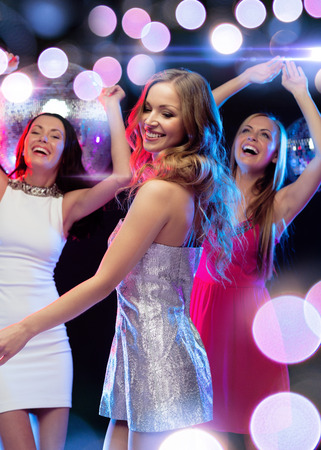 new year, celebration, friends, bachelorette party, birthday concept - three beautiful woman in evening dresses dancing in the club Imagens