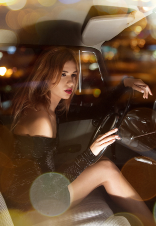 vehicle and lifestyle concept - glamorous woman behind the wheel in the car photo