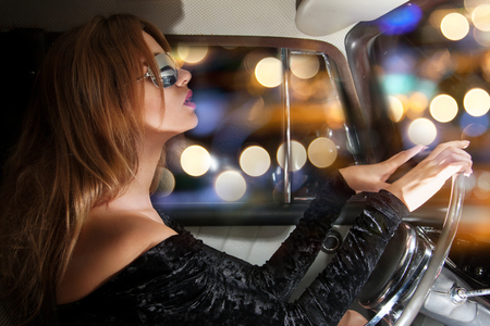 vehicle and lifestyle concept - glamorous woman in sunglasses behind the steering wheel in the car photo