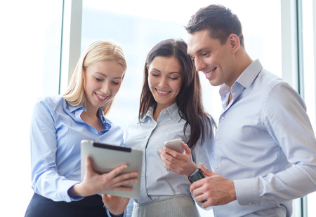 mobile app: business and office concept - smiling business team working with tablet pcs and smartphones in office Stock Photo