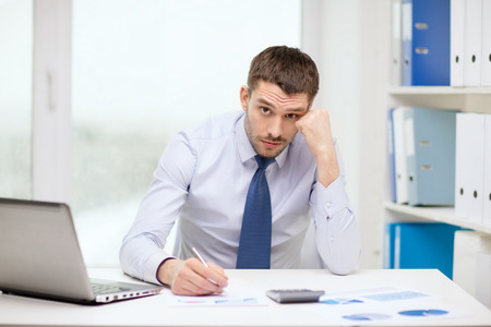 office, business, technology, finances and internet concept - stressed businessman with laptop computer and documents at office photo