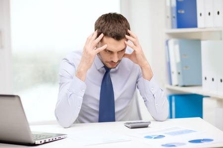 persona confundida: oficina, negocio, la tecnología, las finanzas y el concepto de Internet - subrayaron hombre de negocios con ordenador portátil y documentos en la oficina