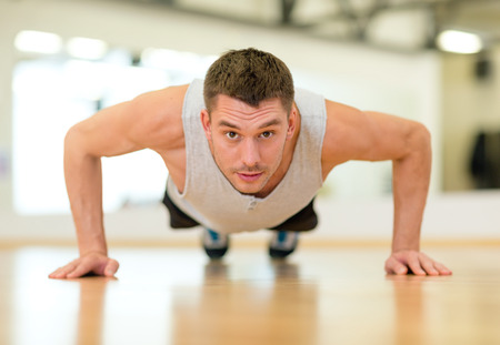 fitness, sport, training, gym and lifestyle concept - concentrated man doing push-ups in the gym photo