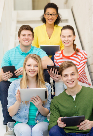 education and technology concept - smiling students with tablet pc sitting on staircase photo