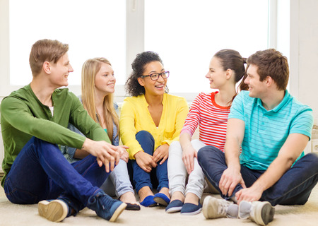 education, leisure and happiness concept - five smiling teenagers having fun at home photo