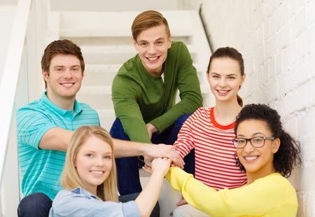 education and happiness concept - smiling students with hands on top of each other sitting on staircase photo