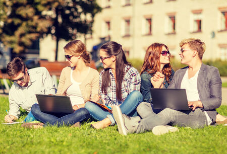 summer, internet, education, technlogy and campus concept - group of students or teenagers with laptop, notebooks and folders photo