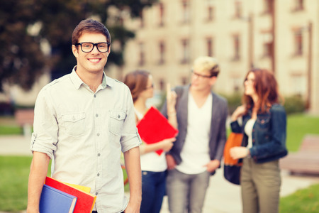 mates: summer holidays, education, campus and teenage concept - smiling teenage boy in eyeglasses with classmates on the back