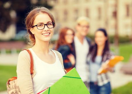 onderwijs: zomervakantie, onderwijs, campus en tiener concept - glimlachende vrouwelijke student in zwarte bril met mappen en de groep in de rug
