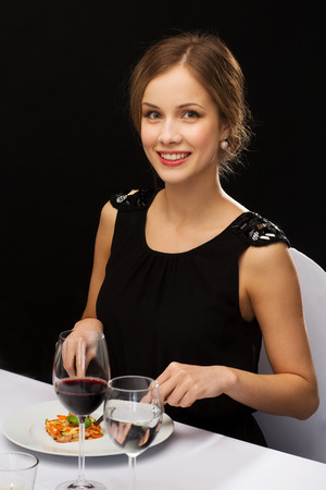 restaurant, people and holiday concept - smiling young woman eating main course at restaurant photo
