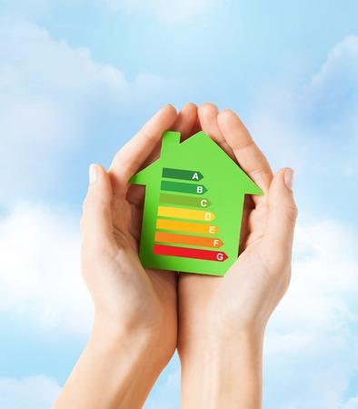 ahorro energetico: ahorro de energ�a, los bienes ra�ces y el concepto de hogar - primer plano de las manos femeninas que sostienen la casa de papel verde con clasificaci�n de eficiencia energ�tica Foto de archivo