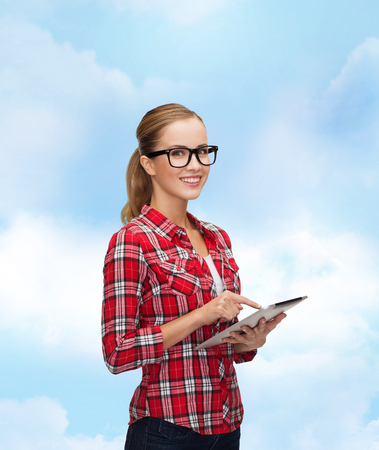 technology, internet and people concept - smiling girl in eyeglasses with tablet pc computer photo