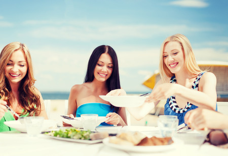 open air: summer holidays and vacation - girls eating and drinking in cafe on the beach