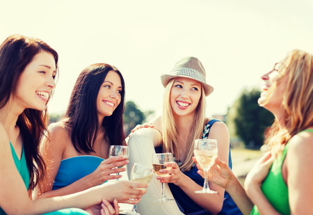 woman drinking wine: summer holidays and vacation - girls with champagne glasses on boat or yacht Stock Photo