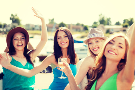 tour boats: summer holidays and vacation - girls with champagne glasses on boat or yacht Stock Photo