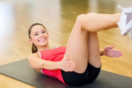 asian abs: fitness, sport, training, gym and lifestyle concept - smiling woman doing exercise on mat in gym
