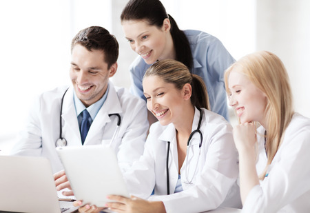 healthcare, medical and technology concept - group of doctors looking at tablet pc photo