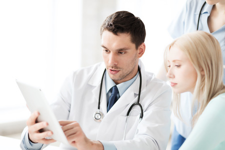 serious doctor: healthcare, medical and technology - doctor showing something patient on tablet pc in hospital Stock Photo