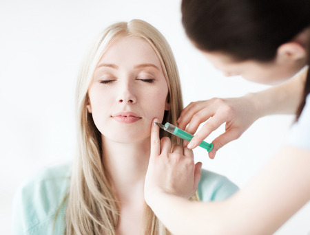 healthcare, medical and plastic surgery - beautician with patient doing botox injection in hospital Stock Photo