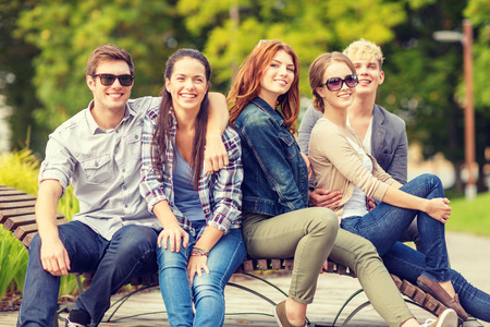 summer holidays, education, campus and teenage concept - group of students or teenagers hanging out outdoors photo
