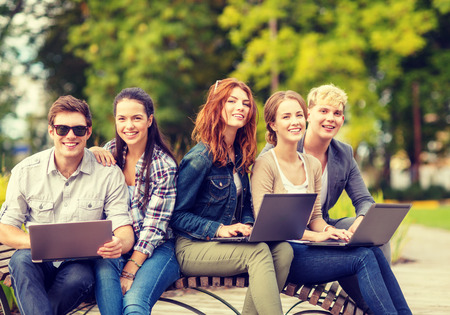 in out: summer holidays, education, campus, technology and teenage concept - group of students or teenagers with laptop computer