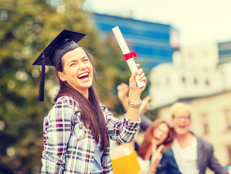 education, campus and teenage concept - smiling teenage girl in corner-cap with diploma and classmates on the back photo
