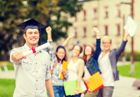 education, campus and teenage concept - smiling teenage boy in corner-cap with diploma and classmates on the back photo