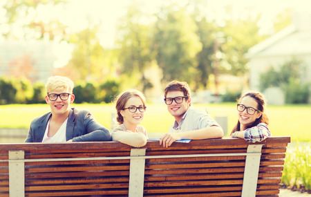 summer holidays, education, campus and teenage concept - group of students or teenagers in eyeglasses hanging out photo