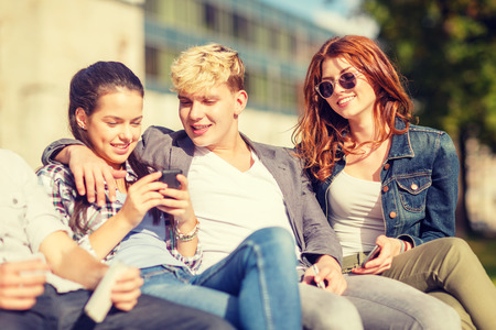 chilling: summer holidays, education, campus, technology and teenage concept - group of students or teenagers with spartphones